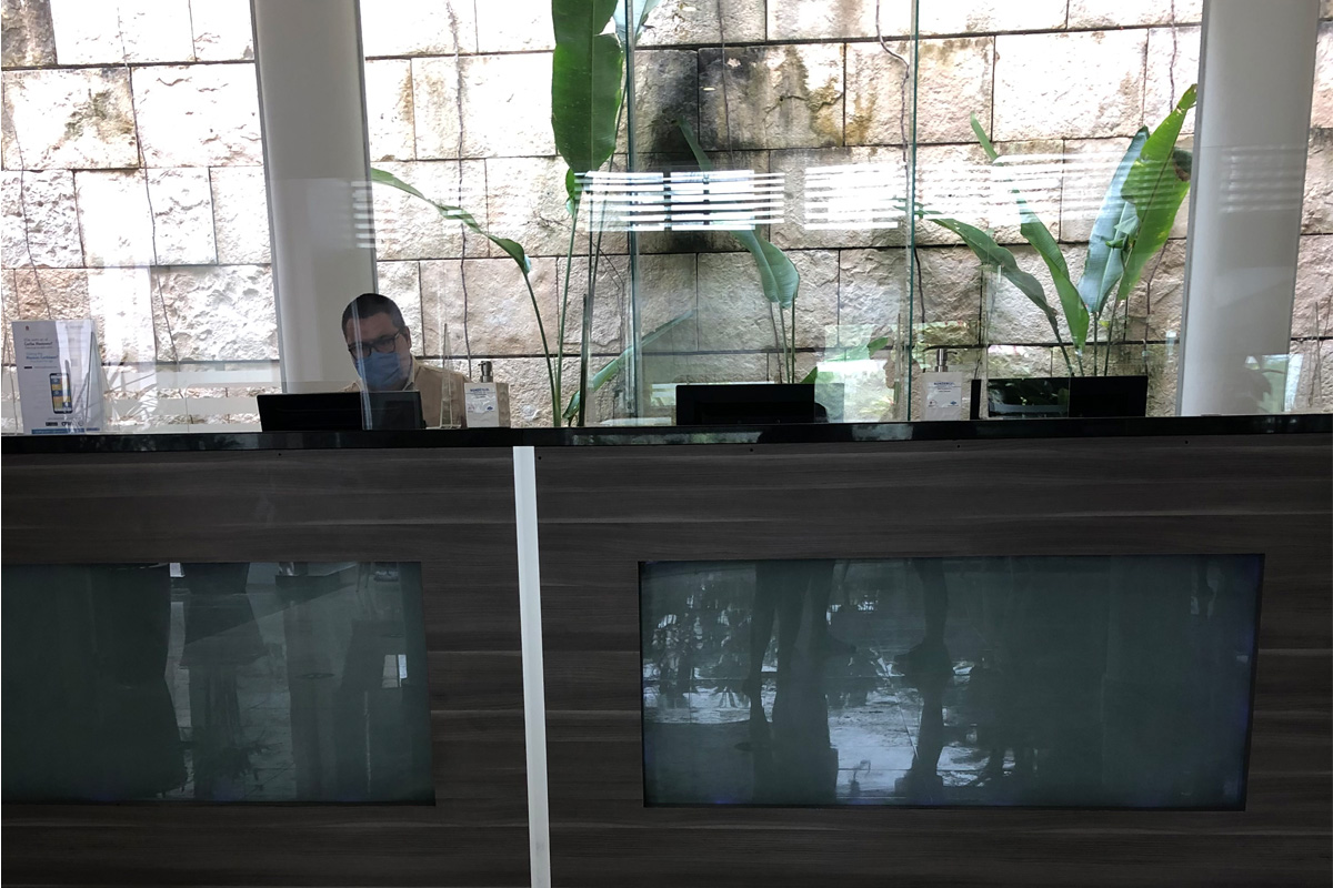 Le personnel est protégé par des vitres en plastique au comptoir d'enregistrement. Photo: Lori Gold.