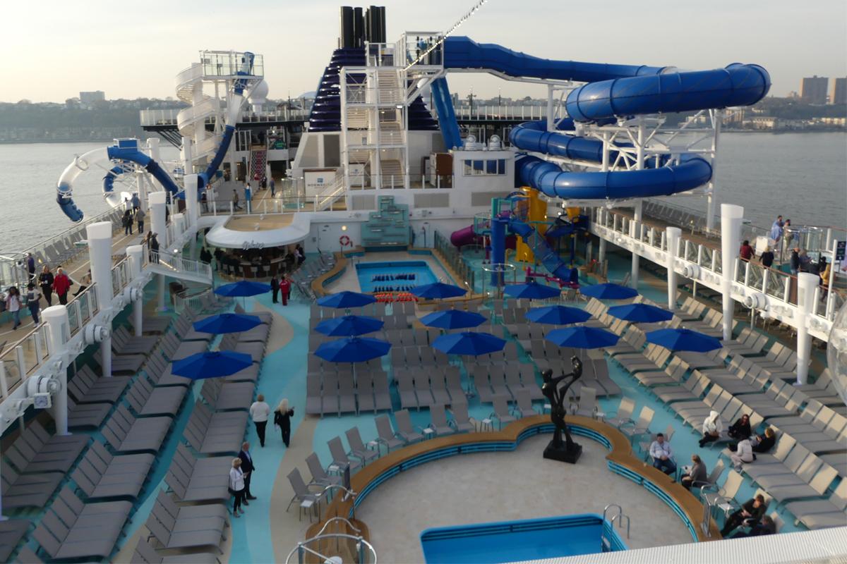La terrasse de la piscine du Norwegian Encore avec toboggans et parc aquatique pour enfants.